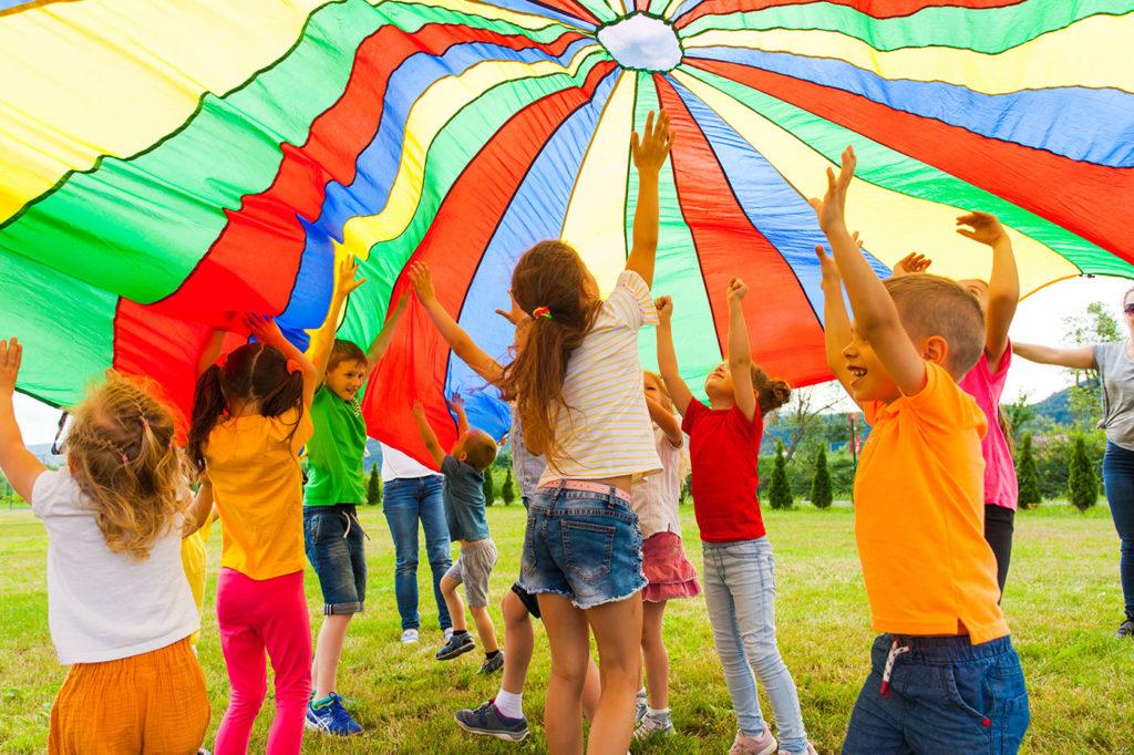 Joyous classmates jumping under colorful parachute at a Preschool & Daycare Serving Greenville, AL