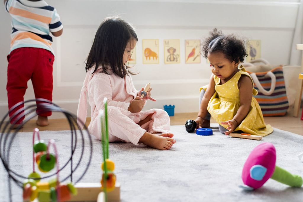 Little kids playing toys in the playroom at a Preschool & Daycare Serving Greenville, AL