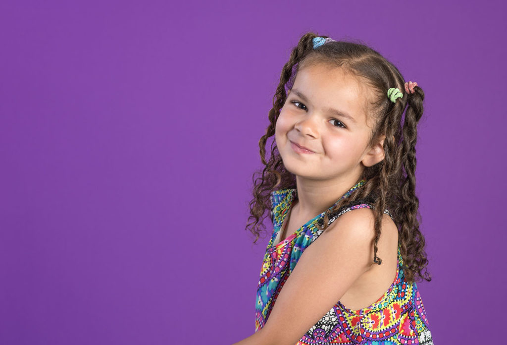 Mixed race little girl with mischievous smile and curly brown hair at a Preschool & Daycare Serving Greenville, AL