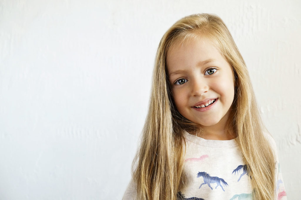 happy little girl with long blonde hair smilng at a Preschool & Daycare Serving Greenville, AL