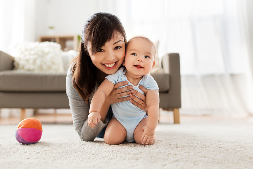 happy smiling young asian mother with little baby at home in Greenville, AL