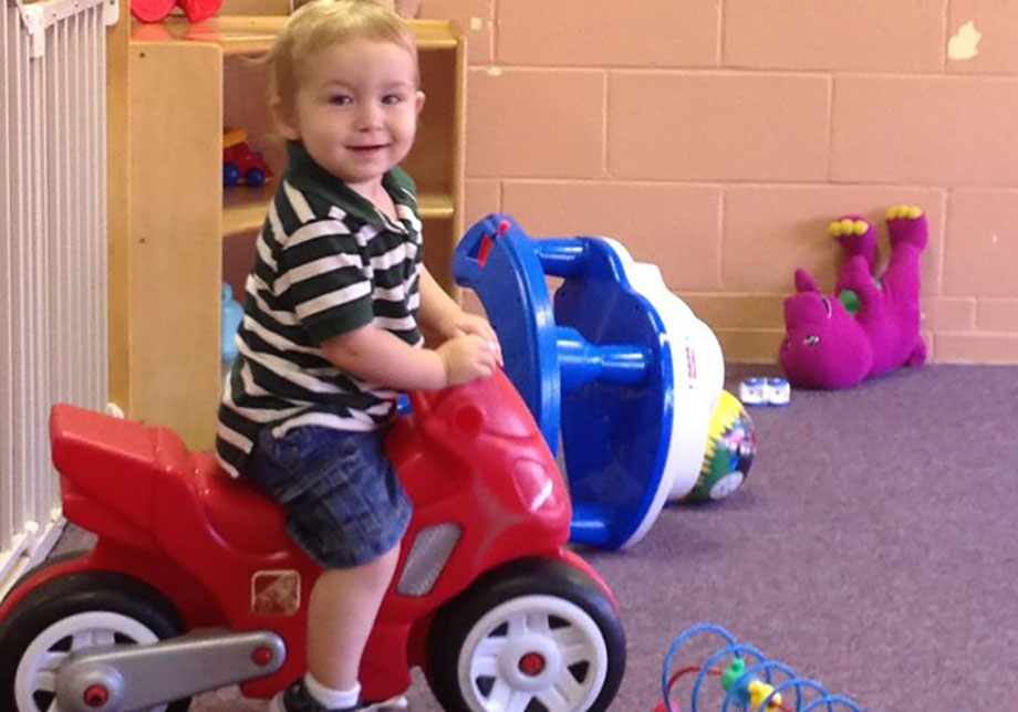 smiling boy on toy motorcycle at a Preschool & Daycare Serving Greenville, AL