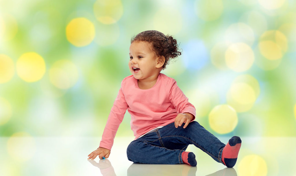 smiling little baby girl sitting on floor at a Preschool & Daycare Serving Greenville, AL