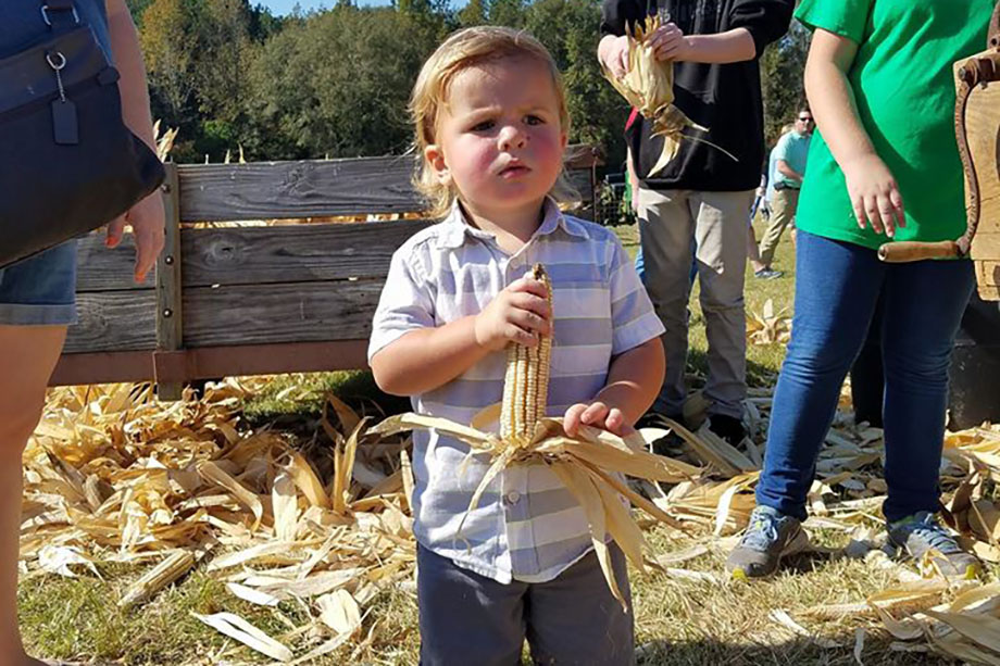 toddler boy holding corn at a Preschool & Daycare Serving Greenville, AL