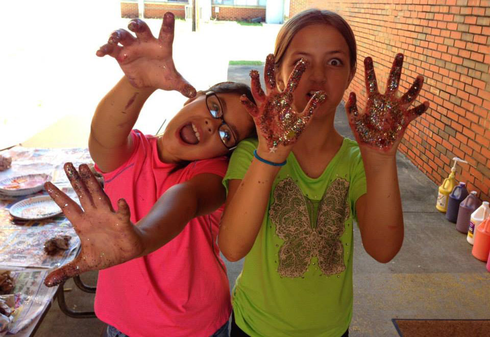 young girls with glitter on hands at a Preschool & Daycare Serving Greenville, AL